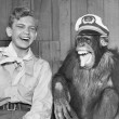 Laughing boy scout and monkey wearing hat...