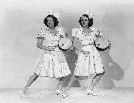 Photo pour Femmes en tenues assorties jouant de la batterie - image libre de droit