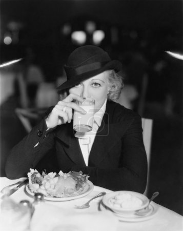 Portrait of woman drinking and eating in restaurant