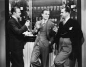 Businessmen drinking together at bar