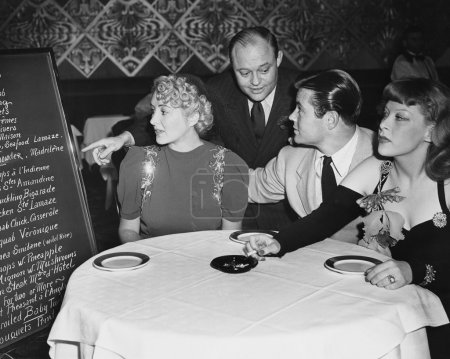 Waiter and customers in restaurant