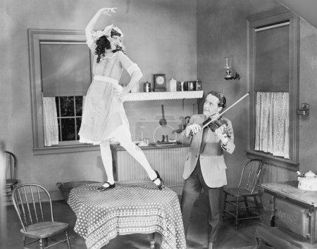 Man playing violin for woman dancing on table