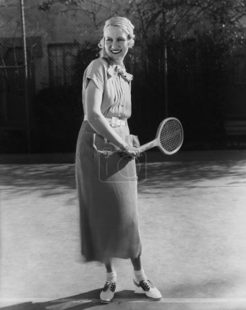 Photo for Smiling woman playing tennis - Royalty Free Image