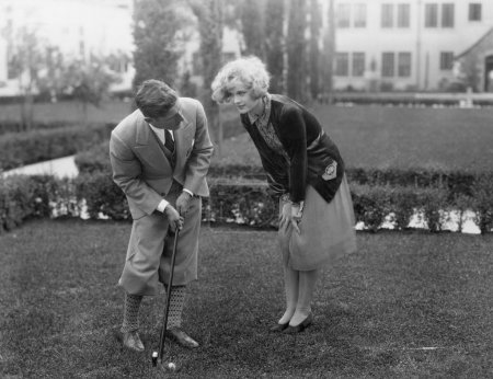 Man talking to woman while golfing