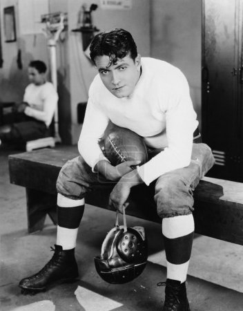 Portrait of football player in locker room...