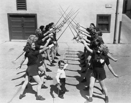 Teenage girls and little boy fencing