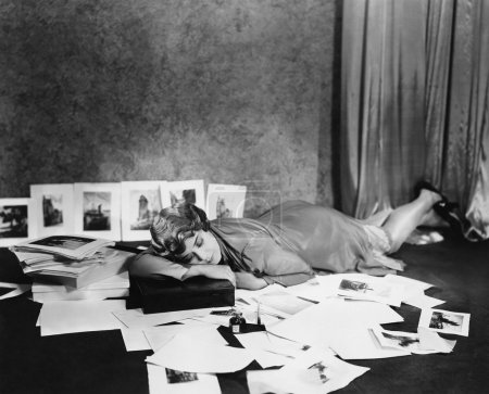 Woman asleep on floor surrounded by illustrations