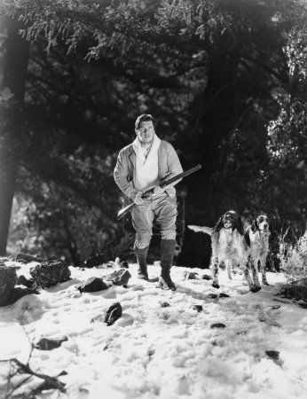 Man hunting in snowy woods with dogs