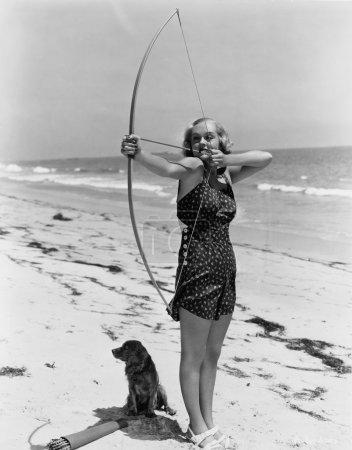 Woman shooting bow and arrow on beach