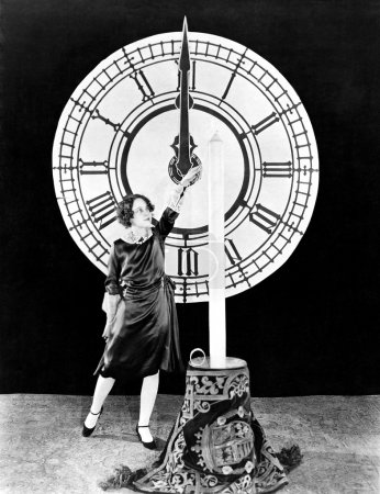 Woman with candle and clock on New Years Eve