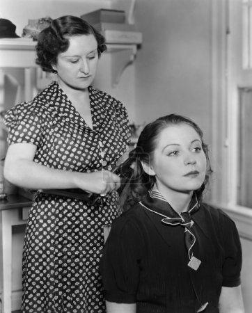 Photo pour Femme coiffant une autre femme cheveux - image libre de droit