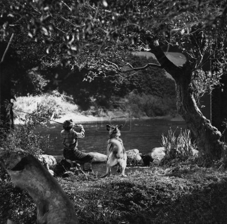 Photo pour Garçon pêche avec chien dans la rivière - image libre de droit