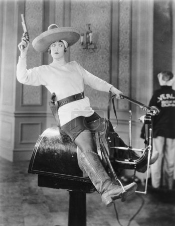 Woman playing cowgirl on mechanical horse