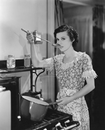 Woman tasting food cooking on stove