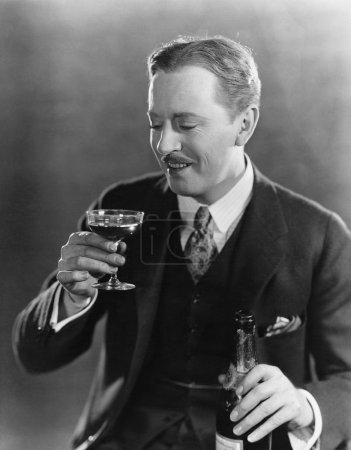Photo for Smiling man with beverage and bottle - Royalty Free Image