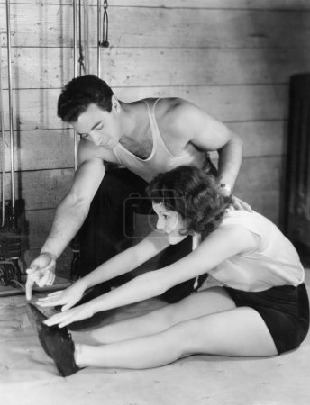 Woman stretching with help from trainer