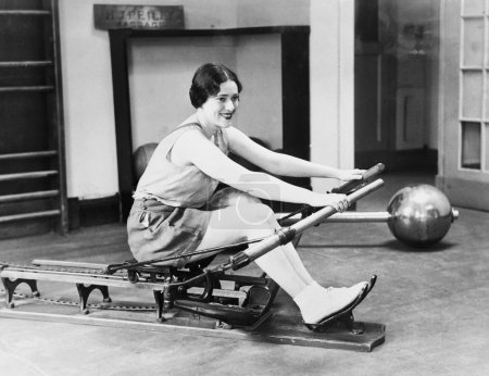 Photo for Woman using rowing machine - Royalty Free Image