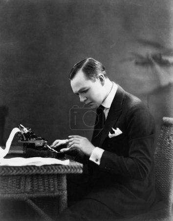 Portrait of man using typewriter
