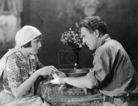 Woman bandaging mans hand