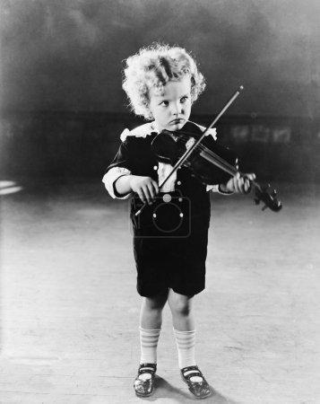 Portrait of little boy playing violin