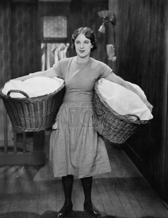 Photo pour Femme portant des paniers à linge - image libre de droit
