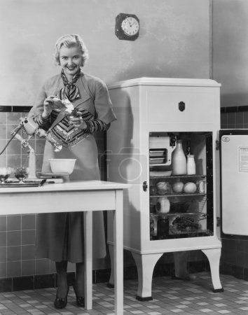 Woman with refrigerator and mixer in kitchen