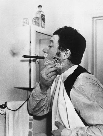 Man smoking cigar and shaving