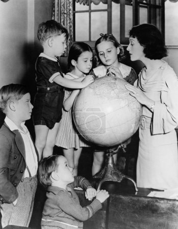 Woman and children looking at globe