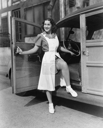 Frau posiert vor Autotür
