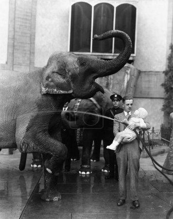 Man holding child and washing elephant