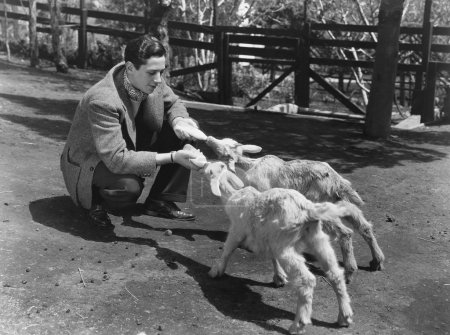 Man feeding two baby goats