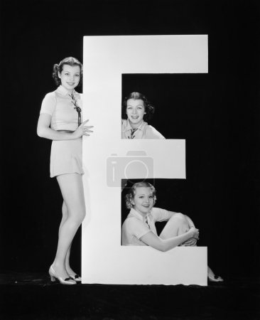Photo for Women posing with huge letter E - Royalty Free Image
