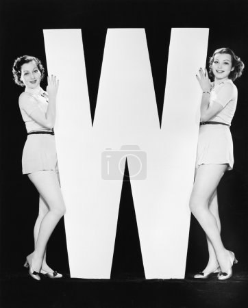 Women posing with huge letter W