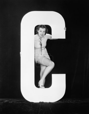 Woman posing with huge letter C