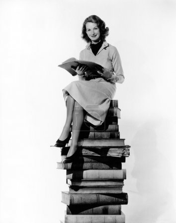 Photo for Woman sitting on pile of books - Royalty Free Image