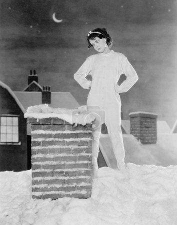 Photo pour Jeune femme regardant cheminée sur le toit enneigé - image libre de droit