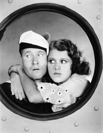 Woman hugging sailor at porthole