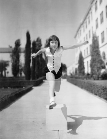 Photo for Girl leaping over wooden blocks - Royalty Free Image