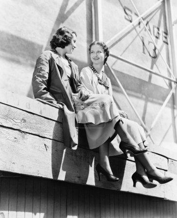 Photo pour Deux femmes assises ensemble sur un échafaudage - image libre de droit