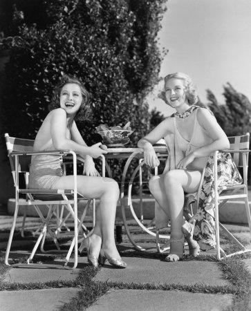 Two women sitting together in a back yard