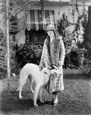 Young woman in coat and hat standing outside with her Russian Wolfhound