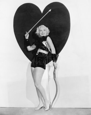 Young woman dressed up as cupid standing in front of a big heart