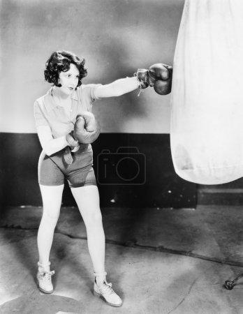Photo pour Jeune femme avec des gants de boxe, s'entraîne avec un sac de boxe - image libre de droit