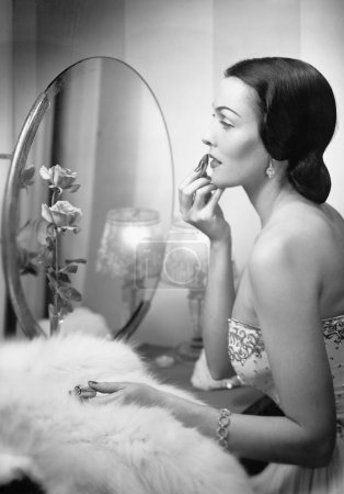 Young woman looking into a mirror and putting on make up