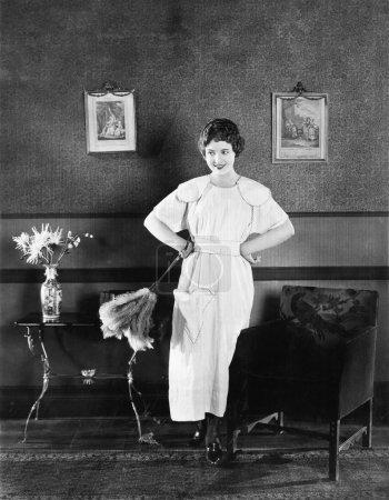 Photo pour Jeune femme dans un tablier et un plumeau debout dans un salon - image libre de droit