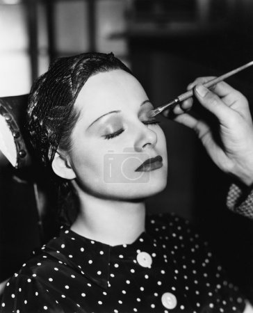 Young woman having make up done