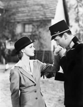 Man in an uniform kissing the hand of a young woman
