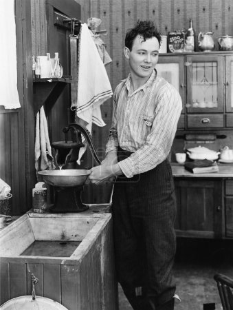 Man in a kitchen pumping water