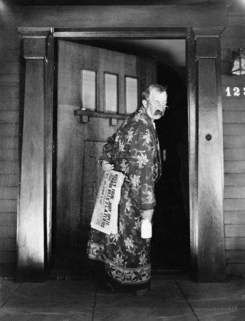 Mann geht mit Zeitung und Milch in der Hand ins Haus