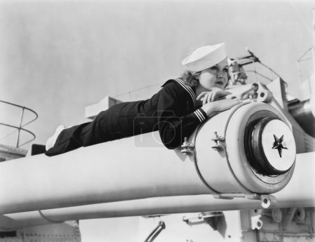 Woman in a sailors uniform lying on a cannon